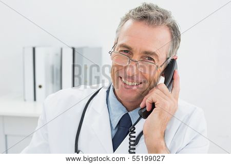 Close-up portrait of a smiling male doctor using telephone at the medical office