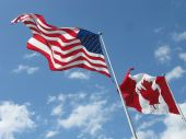 image of usa flag  - Large American and Canadian flags fly side by side wind - JPG