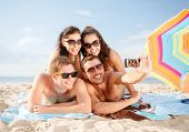 summer, holidays, vacation, technology and happiness concept - group of smiling people in sunglasses