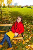 stock photo of 11 year old  - Autumn portrait of a 11 years old girl sitting on the bench in the park after school with paper folder - JPG