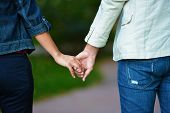 stock photo of middle finger  - Lovely couple holding hands in the middle of summer - JPG