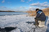 stock photo of auger  - The fisherman on winter fishing in frosty day - JPG