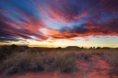 stock photo of dune  - Beautiful kalahari sunset with dramatic clouds and grass on sand dune - JPG