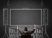 pic of home theater  - Young businessman sitting and enjoying home cinema system sketched on a chalkboard - JPG
