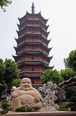 Smiling Buddha Statue In Front Of A Distorted Ruigang Pagodda, Suzhou, China