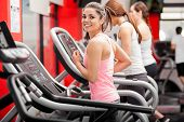 foto of treadmill  - Pretty girl working out in a treadmill at the gym and smiling - JPG