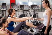 image of rep  - Cute female friends chatting and hanging out in a gym while exercising