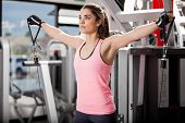picture of pulley  - Beautiful brunette using pulleys to tone her muscles at the gym