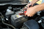 picture of dead-line  - Car mechanic uses battery jumper cables to charge dead battery - JPG