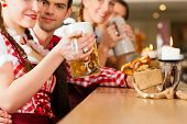 image of stein  - Young people in traditional Bavarian Tracht in restaurant or pub with beer and steins - JPG