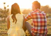 stock photo of couple sitting beach  - back view of young happy couple sitting on river at sunset - JPG