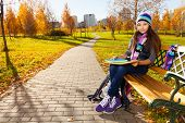 stock photo of 11 year old  - Cute 11 years old girl in warm clothes in the park sitting on the bench in autumn park - JPG