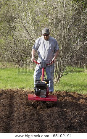 Man Gardening With Rototiller