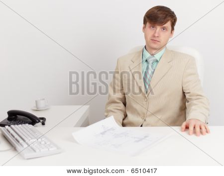 Serious Businessman Sits On Workplace At Office