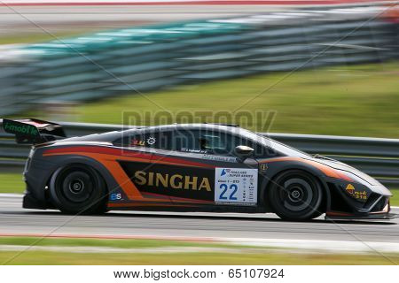 SEPANG, MALAYSIA - MAY 11, 2014: Driver Sanchai Engtrakul in a Lamborghini LP600 car speeds off after turn 2 of the Sepang International Circuit during the Thailand Super Car GT3 race.