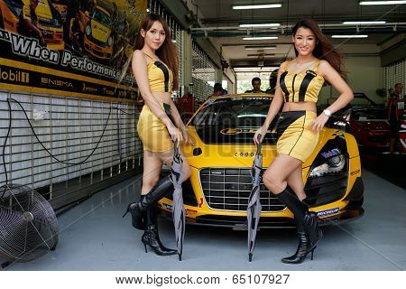 SEPANG, MALAYSIA - MAY 11, 2014: The B-Quik Racing Team grid girls pose with the team car, an Audi R8 LNS at the pit lane at the Thailand Super Series Round 1 in Sepang International Circuit.