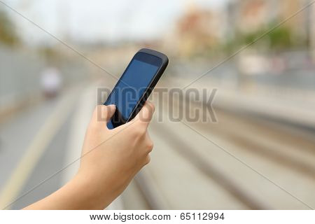 Woman Hand Holding A Smart Phone In A Train Station