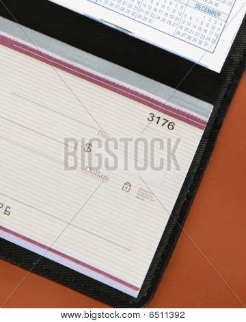 Checkbook On Brown Leather Background