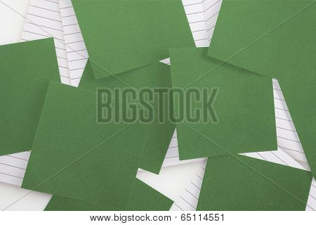 Green paper strewn over notepad paper