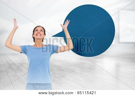 Pretty brunette gesturing with speech bubble against room with holographic cloud