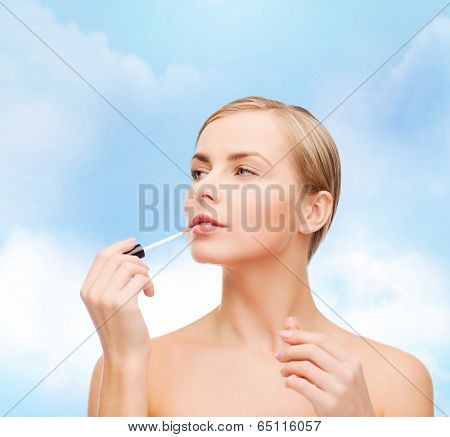 cosmetics, health and beauty concept - beautiful woman with pink lipgloss