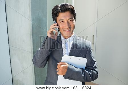 Confident estate agent standing at front door on the phone outside a house
