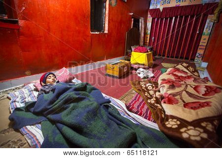 KATHMANDU, NEPAL - DEC 9, 2013: Unknown child sleeping after lesson at Jagadguru School. School established at 2013, to let new generation learn Sanskrit and preserve Hindu culture.