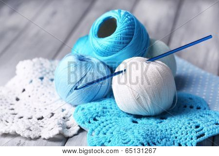 Colorful clews, napkin and crochet hook on wooden background