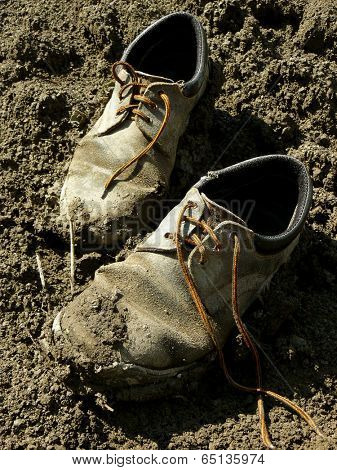 muddy worn out shoes in the dirt