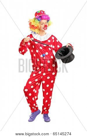 Full length portrait of a female clown holding a magician hat isolated on white background