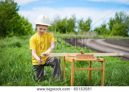 Boy sawing a wooden board outdoors.