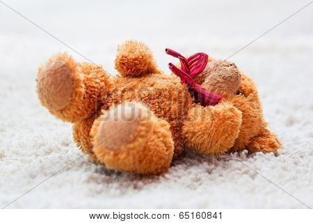Forgotten teddy bear left on the carpet