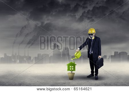 Businessman Watering Plant Under Air Pollution