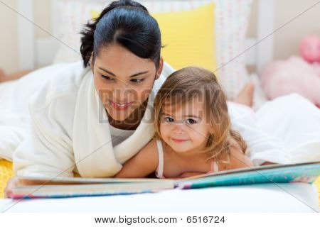 Cute Little Girl Reading A Book With Her Mother