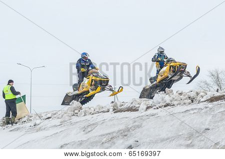 Jump of two sportsmen on snowmobile