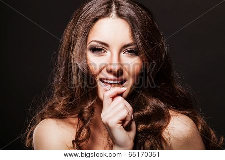 Portrait young woman nibbling the bar of chocolate