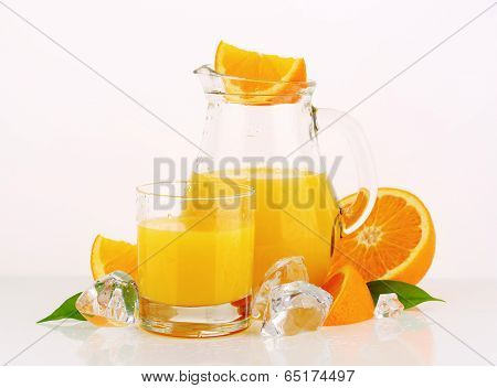 freshly squeezed citrus juice in the glass and pitcher, accompanied with fresh oranges and ice cubes