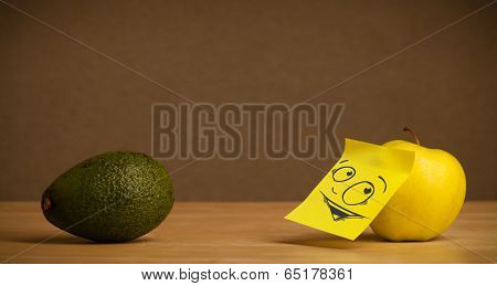 Apple with sticky note reacting at avocado