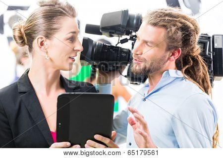 Team discussion or Director giving cameraman scene direction on set of a video production for TV or News