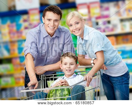 Family drives shopping trolley with food and boy sitting there with watermelon. Concept of fresh and healthy food and consumerism