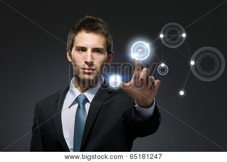 Businessman working with hightech touchscreen pressing buttons on it, isolated on black background