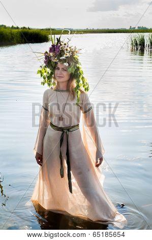 Beautiful sad woman with flower wreath