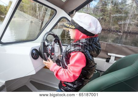 Small Child Driving Motorboat As Captain On Deck