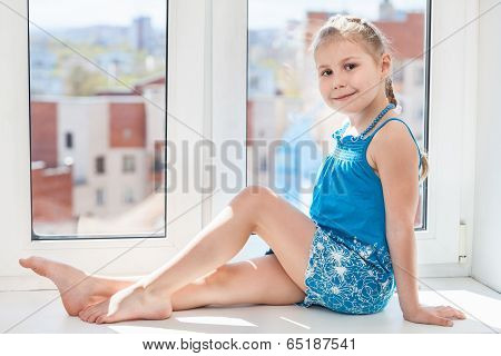 Girl In Blue Dress Sitting On Window Sill In Sun Light