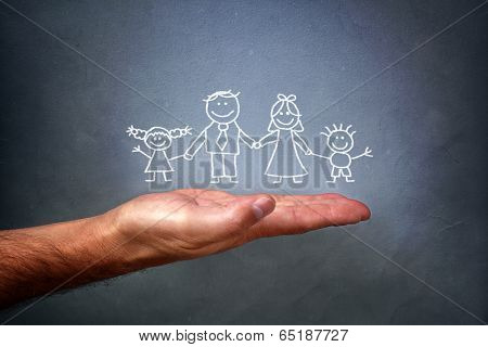 Children's chalk drawing on a blackboard of a happy family with mom, dad, son and daughter holding hands being held in the palm of a mans hand