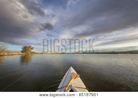 canoe bow with a paddle on a lake - wide angle fisheye perspective - Lonetree Reservoir near Loveland, Colorado