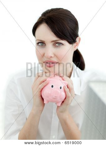 Serious Businesswoman Holding A Piggybank