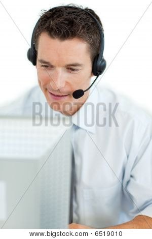 Businessman With Headset On Working At A Computer