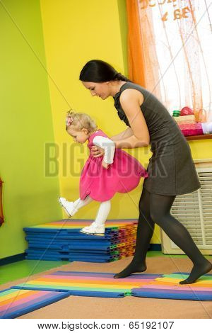 Mother And Child Girl Playing In Montessori Kindergarten .