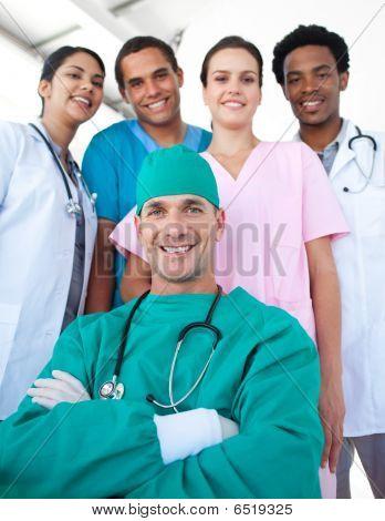 Equipo médico internacional con un cirujano confía en primer plano